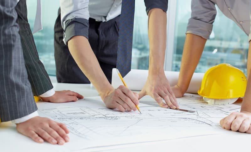 three people leaning on a table with a blueprint